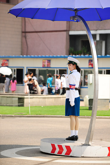 Dolled up in blue and white uniforms, pretty girls work the middle of intersections.